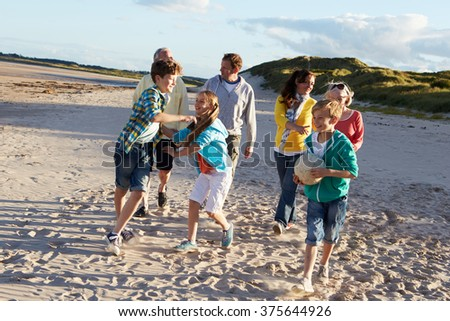 Extended Family Group Walking Along Beach - stock photo