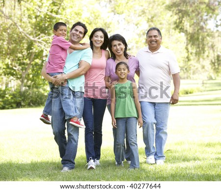Extended Family Group Walking In Park - stock photo