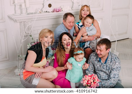 Extended Family Relaxing Together at the fireplace - stock photo