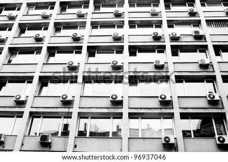 Exterior building with air conditioning in nearly every window. monochrome photo - stock photo