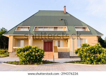 Exterior Front of Luxury Yellow Home with Lush Flower Shrubs Lit with Warm Sunlight, Sloping Green Roof with Balcony and Front Door - stock photo