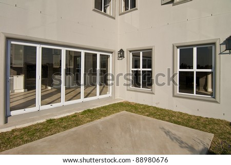 Exterior of a modern house, with a patio and grass - stock photo