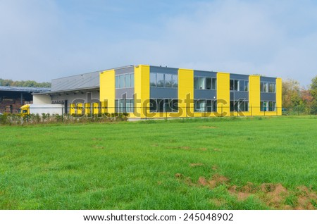 exterior of a yellow office building with warehouse
