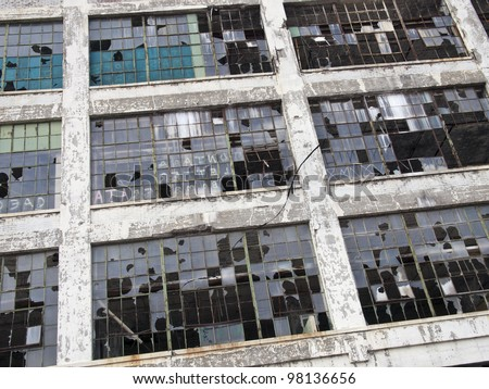 Exterior of an abandoned automobile manufacturing plant in Detroit Michigan. Most of the windows are broken. - stock photo