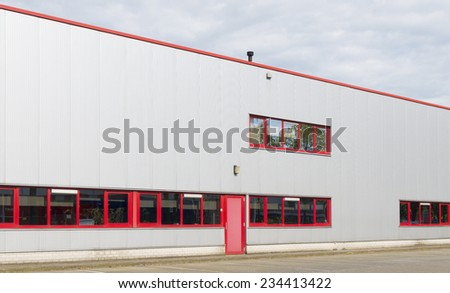exterior of an industrial building with red doors and windows - stock photo