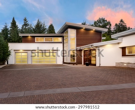 Exterior of large, luxury home with expansive driveway with colorful sunset backdrop - stock photo