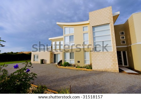 Exterior of modern private house with gravel driveway - stock photo