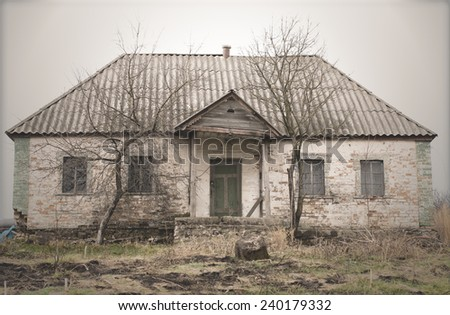 Exterior of Old Abandoned and Weathered Single Storey House with Bare Trees in Front - stock photo