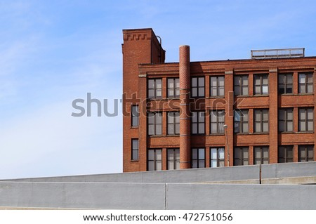 Exterior of old brick warehouse / office building. Light blue sky in background with room for copy. Freeway exit ramp in foreground. Cleveland, Ohio.