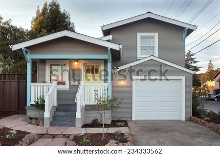 Exterior of remodeled traditional quaint coastal style home with porch and Garage on the West Coast at twilight. - stock photo