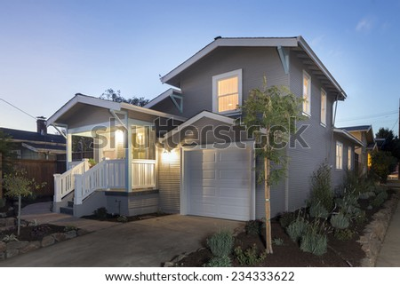 Exterior of remodeled traditional quaint coastal style home with porch and garage on the West Coast at twilight dusk. - stock photo