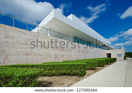 Exterior of the modern style building with beautiful garden with hedges. Manicured shrubs lines. - stock photo