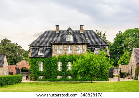 Exterior of the three-story house of light brick with a brown tiled roof. The facade of the house are entwined with green ivy and hedges, Copenhagen, Denmark - stock photo