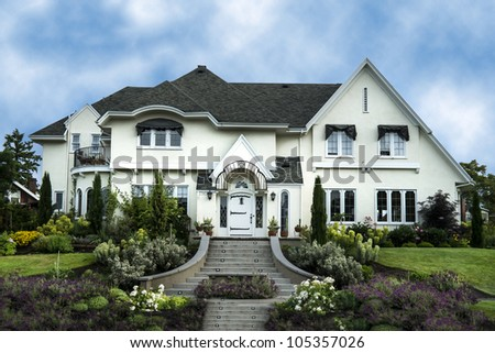 Exterior of white stucco luxury house with landscaped yard - stock photo