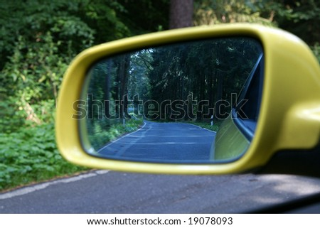 exterior rear view mirror with rural woodlands - stock photo