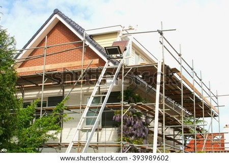 Exterior renovation of a modern house and construction equipments  - stock photo