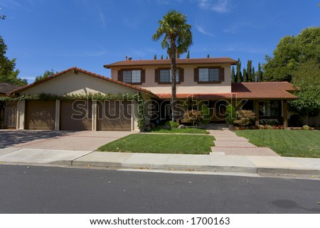 Exterior shot of a Spanish style home with a tile roof.