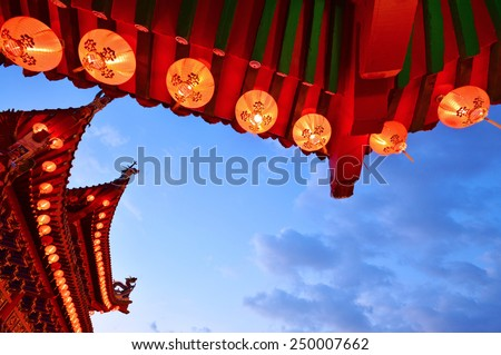 Exterior shot of a temple with the red lanterns against blue skies taken at sunset. - stock photo