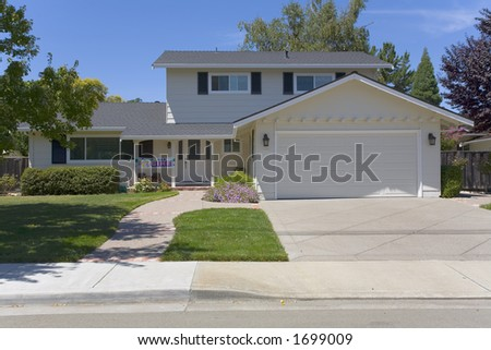 Exterior shot of a very cleanly landscaped two-Story home. - stock photo