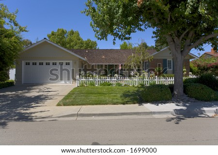 Exterior shot of a very nice single story home with a picket fence. - stock photo