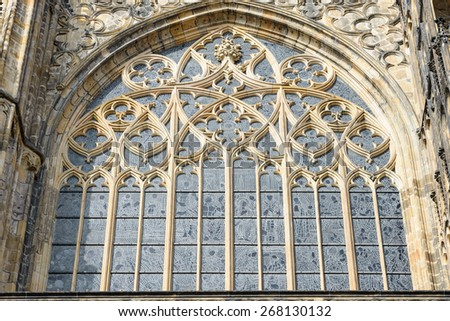 Exterior view of stained-glass window with tracery of cut stone in wide pointed arch above Golden Gate of St. Vitus Cathedral, Prague, Czech Republic. - stock photo