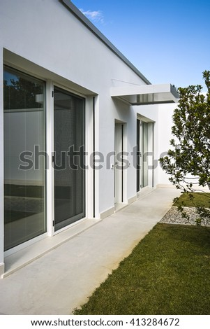 exterior view of the facade of  villa in foreground the entrance - stock photo