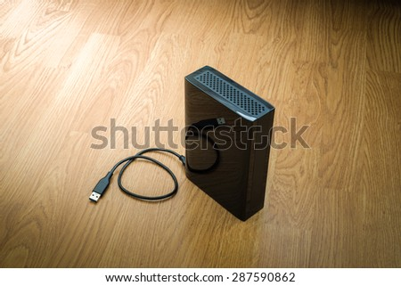 External hard drive on wooden background - stock photo