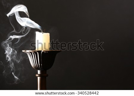 Extinguished candle in candlestick with smoke on dark background - stock photo