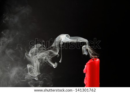Extinguished candle with smoke trailing off the wick - stock photo