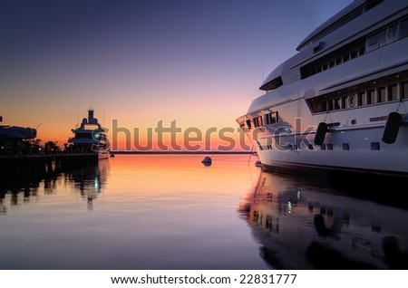 Extra Large Luxury yachts rest in the port at sunset - stock photo