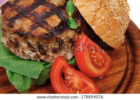 extra thick hot beef meat hamburger dinner on wooden plate with tomatoes and salad isolated on white background - stock photo