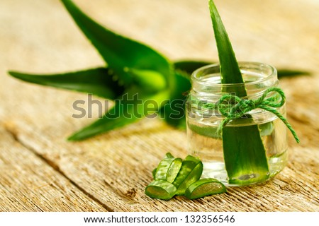 Extract of organic aloe vera gel on wooden background - stock photo