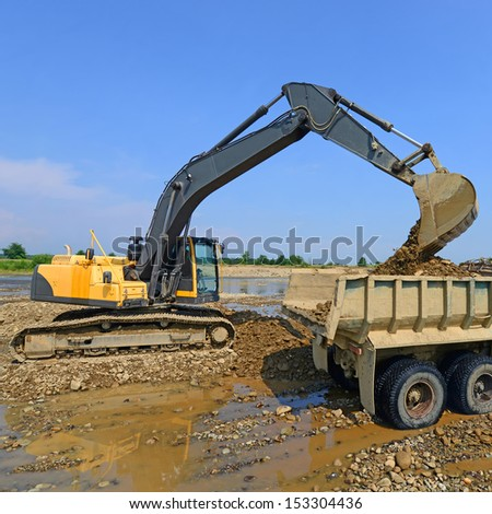 Extracting and loading gravel  - stock photo