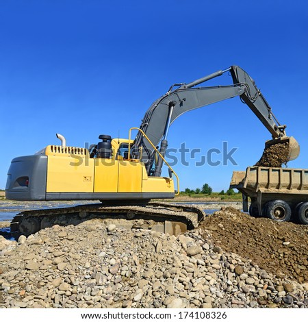Extracting and loading gravel excavated  - stock photo