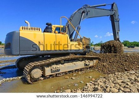 Extracting and loading gravel excavated in the mainstream of the river - stock photo