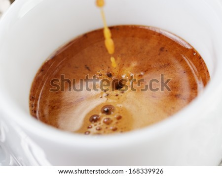 extraction of espresso with rich crema in cup, close up photo - stock photo