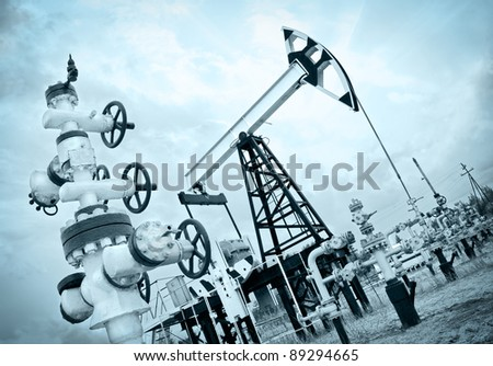 Extraction of oil. Pump jack and oil wellhead. Toned. - stock photo