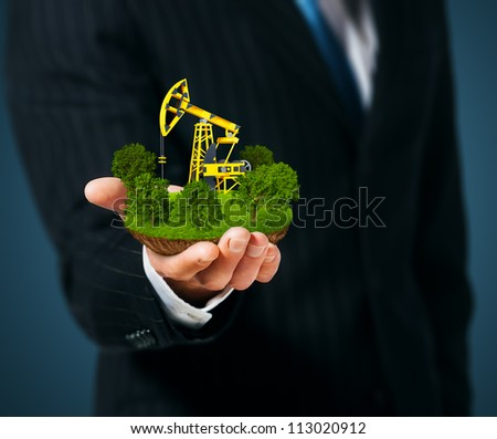 Extraction of oil. Pump jack on men's hand