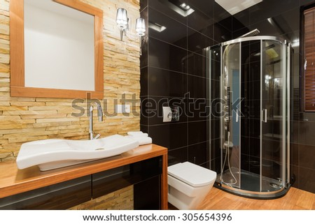 Extravagant decor of new bathroom with black tiles - stock photo