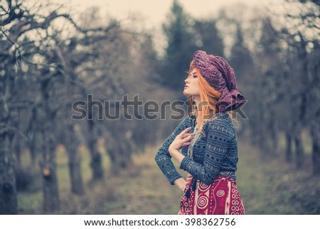 Extravagant exotic beautiful young woman with red hair in a turban in parti-colored dress with elegant patterns posing in winter cold park among trees bent
