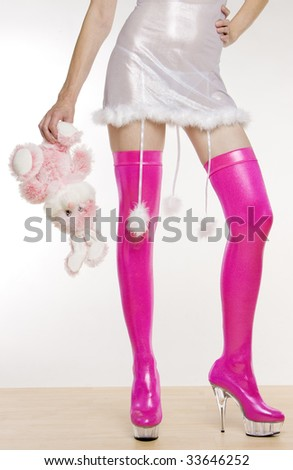 extravagant pink boots and hand holding a rabbit toy
