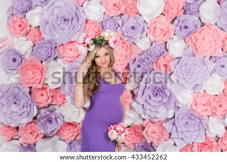 Extravagant young beautiful pregnant woman with long blond hair with a belly is against the floral wall with a wreath of peonies on their heads vintage purple dress - stock photo