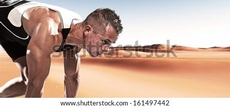 Extreme athlete runner man in starting position outdoor in desert on hot summer day. - stock photo