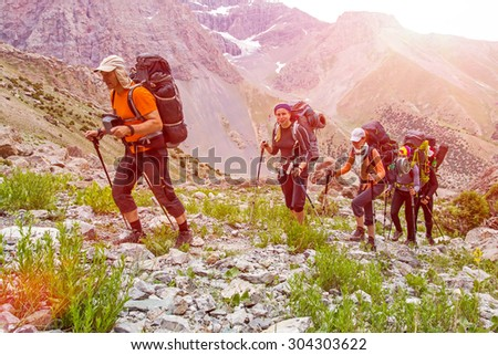 Extreme climbers scrambling up. Group people approach high altitude mountain climbing camp with heavy backpacks tons alpine gear walking on rocky path trail at peaks glaciers snow sun sky background - stock photo