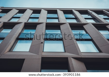 Extreme Close Up and Low Angle View of Modern Commerical Low Rise Office Building with Windows and Brown Stone Pillars Against Hazy Blue Sky - Abstract Architectural Background - stock photo