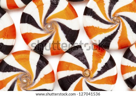 Extreme close-up cropped shot of identical colorful hard candies with swirl pattern. - stock photo