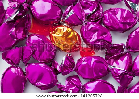 Extreme close-up image of a golden candy arranged purple hard candies over white. - stock photo