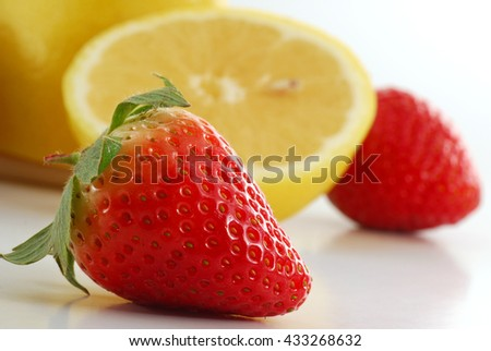 Extreme close-up image of a strawberry with more fruit in background