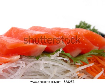 Extreme close up of a plate with raw salmon meat and some vegetables,radish and carrots.