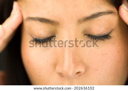 Extreme close-up of a young woman suffering with headache - stock photo